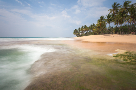 A wonderful nature landscape of a beach scene in Sri Lanka. Sky with clouds, ocean surf and golden sand with palms are the perfect paradise atmosphere.