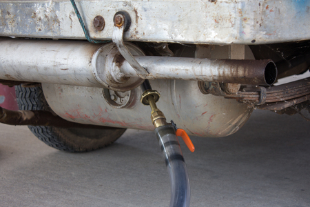 to fill up: Car at gas station being filled with fuel, fill up of liquefied petroleum gas, LPG Stock Photo