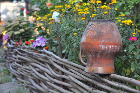 rural scenery - old clay pots on a wattled fence near flowers Stock Photo