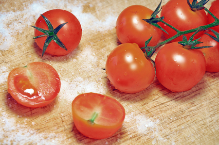 wet  red tomatoes on a branch  on a wooden board with salt Stock Photo