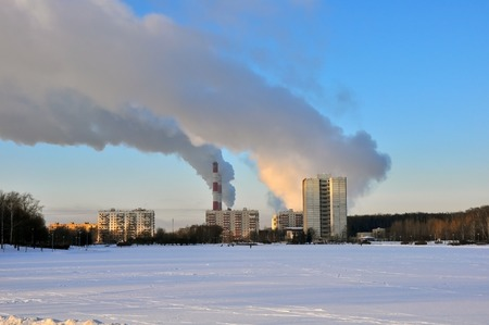 winter city and industrial smoke clouds the sky Stock Photo