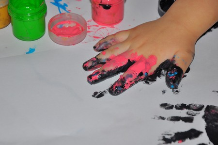 the childrens hand soiled in black and pink paints