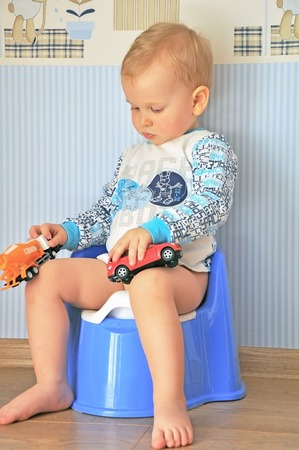 the blonde little boy with pouted sitting on the pot with his toys