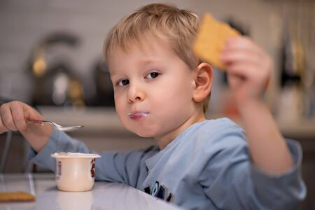 Adorable little blonde boy eating yogurt with a spoon