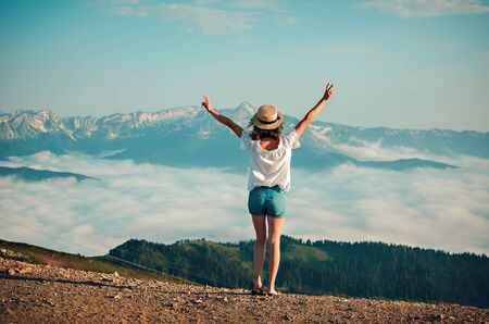 the girl in a straw hat costs at top of the mountain and looks afar at clouds. View from a back