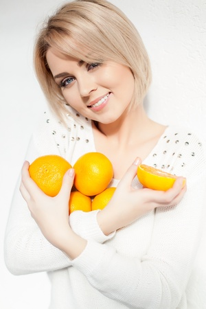 blonde close up: Portrait of a beautiful young and healthy women blonde with expressive eyes and a bob hairstyle  Poses in front of a white wall with yellow tangerines in hands  Stock Photo