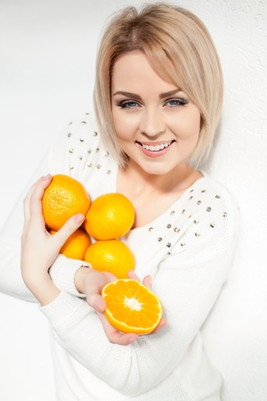 Portrait of a beautiful young and healthy women blonde with expressive eyes and a bob hairstyle  Poses in front of a white wall with yellow tangerines in hands  photo