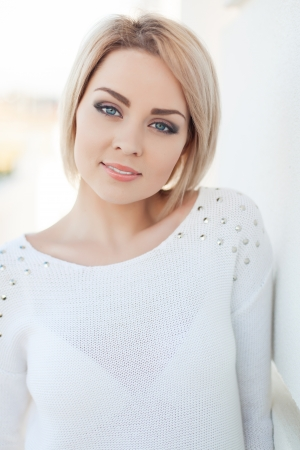 Portrait of a beautiful young and healthy women blonde with expressive eyes and a bob hairstyle. Poses in front of a white wall.