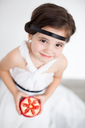 Portrait of a cute little girl model looks in luxurious white dress with makeup and hair decoration. Posing against a white wall with a pomegranate in her hand. Stock Photo - 16253298