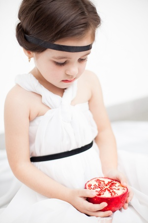 Portrait of a cute little girl model looks in luxurious white dress with makeup and hair decoration. Posing against a white wall with a pomegranate in her hand. Stock Photo - 16253277