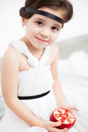 Portrait of a cute little girl model looks in luxurious white dress with makeup and hair decoration. Posing against a white wall with a pomegranate in her hand. Stock Photo - 16253272