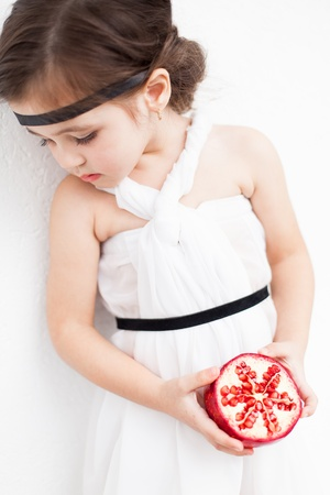 Portrait of a cute little girl model looks in luxuus white dress with makeup and hair decoration. Posing against a white wall with a pomegranate in her hand. Stock Photo - 16253291