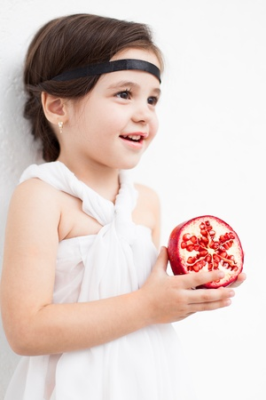 Portrait of a cute little girl model looks in luxurious white dress with makeup and hair decoration. Posing against a white wall with a pomegranate in her hand.
