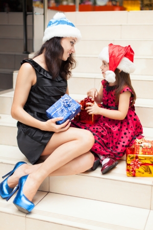 Mom and daughter posing with gifts in the Christmas hat and a luxurious dress, sitting on the stairs in a big shopping mall. Stock Photo - 16253309