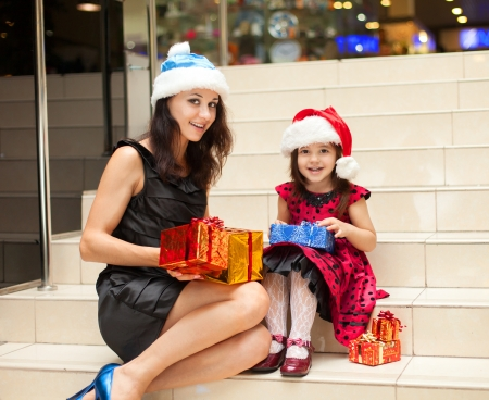 Mom and daughter posing with gifts in the Christmas hat and a luxurious dress, sitting on the stairs in a big shopping mall. Stock Photo - 16253233