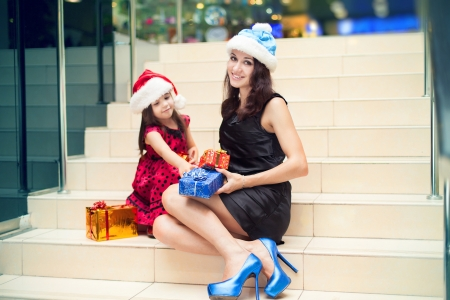 Mom and daughter posing with gifts in the Christmas hat and a luxurious dress, sitting on the stairs in a big shopping mall. Stock Photo - 16253182