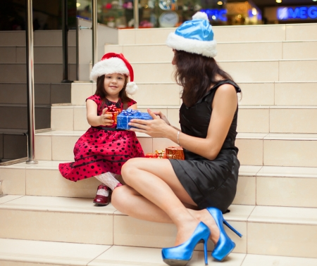 Mom and daughter posing with gifts in the Christmas hat and a luxuus dress, sitting on the stairs in a big shopping mall. Stock Photo - 16253293