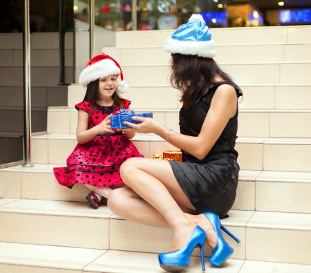 Mom and daughter posing with gifts in the Christmas hat and a luxurious dress, sitting on the stairs in a big shopping mall. photo