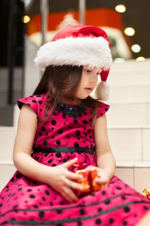 Cute little girl posing with gifts in the Christmas hat and a luxurious dress, sitting on the stairs in a big shopping mall. Stock Photo - 16253311