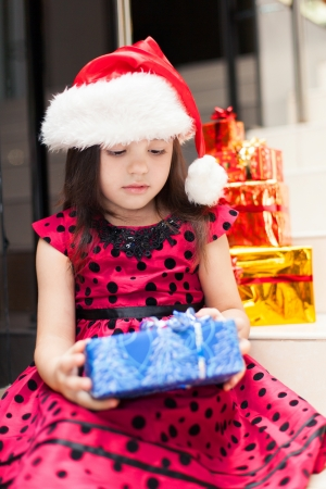 Cute little girl posing with gifts in the Christmas hat and a luxurious dress, sitting on the stairs in a big shopping mall. Stock Photo - 16253190