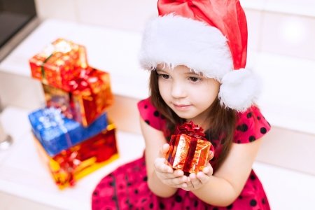 Cute little girl posing with gifts in the Christmas hat and a luxuus dress, sitting on the stairs in a big shopping mall. Stock Photo - 16253178