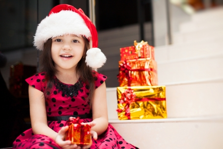 Cute little girl posing with gifts in the Christmas hat and a luxurious dress, sitting on the stairs in a big shopping mall. photo