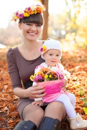 Family portrait cute little girl and cheerful mom. Posing in a park on a background of autumn leaves and bright colors. Stock Photo - 16253341