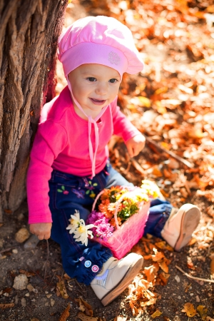Portrait of a cute little baby posing in autumn park against fallen yellow leaves