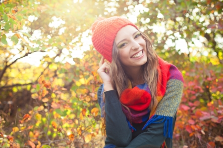 Happy elegant young woman in a knitted red hat posing against colorful fall forest. Early autumn in October.