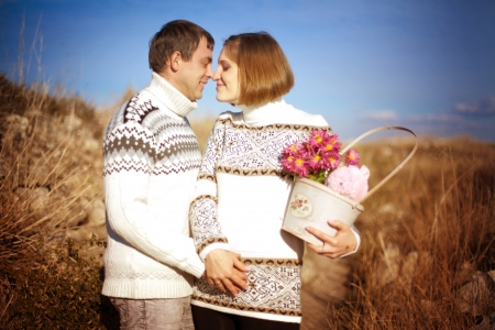 In love beautiful family, a loving husband and a pregnant wife posing on a background of yellow grass and blue sky in the park. Warm early autumn. Stock Photo