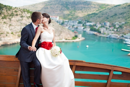 manhood: Young couple in love the bride and groom with a bouquet posing on the background beautiful mountains and bays of the wedding day in the summer  Enjoying a moment of happiness and love
