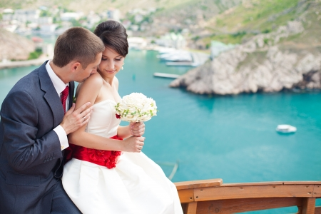 Young couple in love the bride and groom with a bouquet posing on the background beautiful mountains and bays of the wedding day in the summer  Enjoying a moment of happiness and love