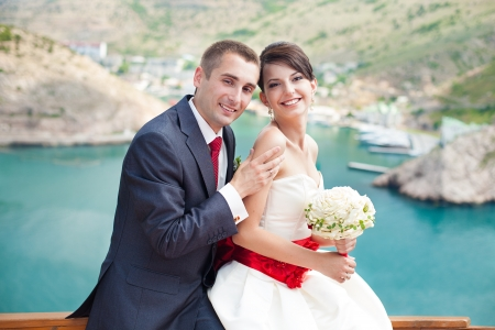 Young couple in love the bride and groom with a bouquet posing on the background beautiful mountains and bays of the wedding day in the summer  Enjoying a moment of happiness and love  photo