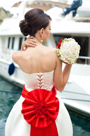 women subtle: The bride with a beautiful bouquet and hair gathered near the boat Stock Photo