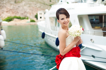 The bride with a beautiful bouquet and hair gathered near the boat photo