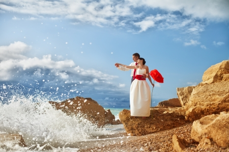 A young couple in love bride and groom with a huge beautiful red rose in her hand posing on the beach in their wedding day photo