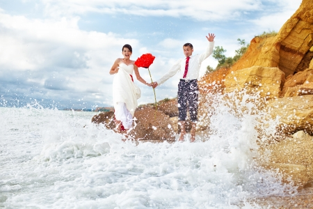A young couple in love bride and groom with a huge beautiful red rose in her hand posing on the beach in their wedding day  Enjoy a moment of happiness and love  photo