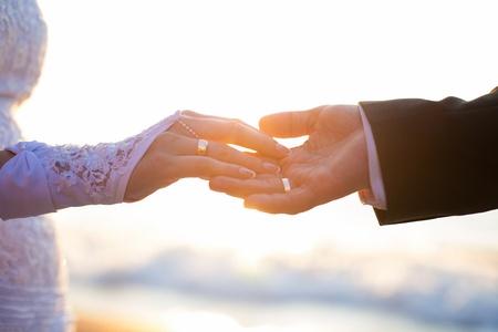 바다와 태양의 배경에 결혼 반지와 함께 손을 잡고
