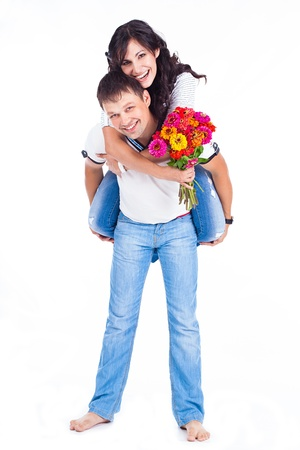 Young couple husband and wife posing with a bouquet of colorful flowers in the studio on a white background