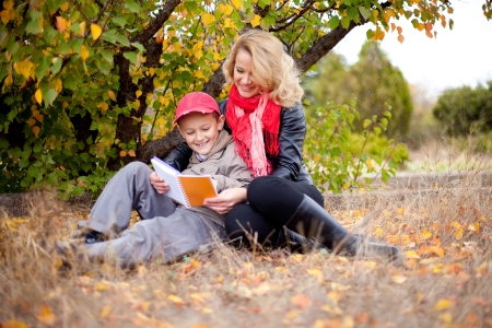 Beautiful family of mother and son posing on a background a tree with yellow leaves and grass gray  Healthy young mother with a luxurious blonde hair  Autumn  photo