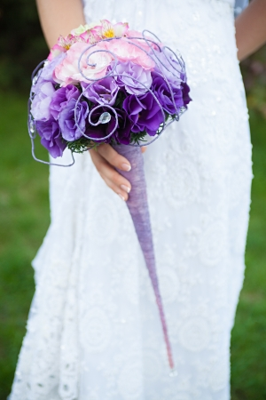 Wedding bouquet of purple and pink flowers in the hands of the bride photo