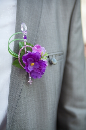 The groom at a wedding ceremony  Boutonniere for gray jacket