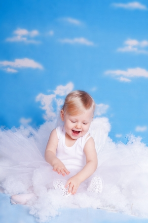 Beautiful baby girl with angel wings in white clothes posing on a background of the sky with clouds - decorated in the style of a little angel in the clouds  Stock Photo