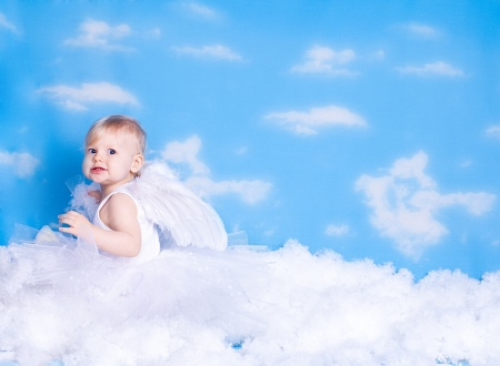 Beautiful baby girl with angel wings in white clothes posing on a background of the sky with clouds - decorated in the style of a little angel in the clouds  A series of photos in my portfolio