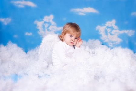 Beautiful baby girl with angel wings in white clothes posing on a background of the sky with clouds - decorated in the style of a little angel in the clouds  A series of photos in my portfolio  photo