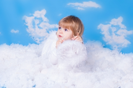Beautiful baby girl with angel wings in white clothes posing on a background of the sky with clouds - decorated in the style of a little angel in the clouds Stock Photo - 16296213