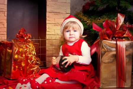 Beautiful blond little girl in a red Christmas hat posing by the fireplace on Christmas Eve, enjoys gifts  A series of photos in my portfolio  Stock Photo - 16292551