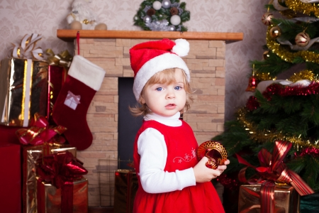 Beautiful blond little girl in a red Christmas hat posing by the fireplace on Christmas Eve, enjoys gifts  A series of photos in my portfolio Stock Photo - 16292506