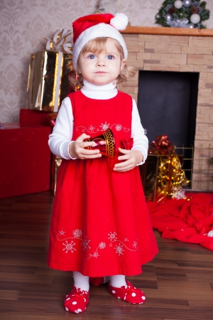 Beautiful blond little girl in a red Christmas hat posing by the fireplace on Christmas Eve, enjoys gifts  A series of photos in my portfolio  Stock Photo - 16292536