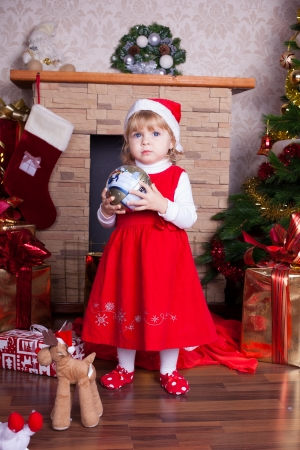 Beautiful blond little girl in a red Christmas hat posing by the fireplace on Christmas Eve, enjoys gifts  A series of photos in my portfolio  Stock Photo - 16292574